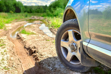 Close-up of an off-road vehicle wheel of SUV. Concept of summer traveling and adventure with a large 4x4 drive car against the background of puddle and mud and bad roads in the forest. Standard-Bild
