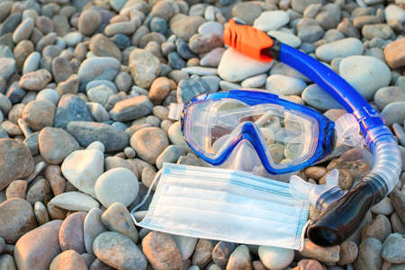 Snorkeling mask and tube and a medical protective mask against the sea pebbles. Concept of summer vacation season in the conditions of the coronavirus Covid-19 pandemic. Professional diving equipment.
