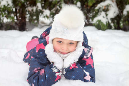 Close-up portrait of a smiling pretty girl in a winter suit and a white hat with a fur pompom lying on the snow. The concept of winter time in nature. Games and activity in the fresh frosty air