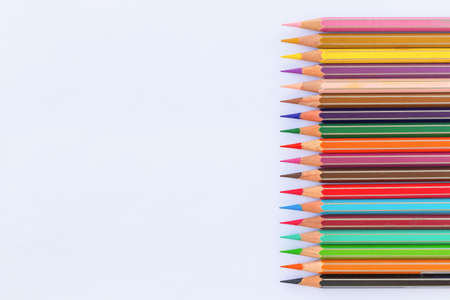 Close-up and flat lay of multicolored professional watercolor pencils on a white paper background with copy space. Concept of teaching young artists and children drawing and art. Tools for painters