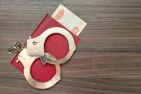 Close-up of metal handcuffs lie on passport with large banknote inside. The concept of criminal liability for offering and receiving monetary bribes. Crime of official. Registration of false documents Stock fotó