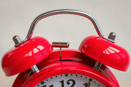 Close-up and selective focus focus of red alarm clock. Concept of morning awakening, time for business and work. Course of life and time. Deadline for important task. Daily schedule, task management
