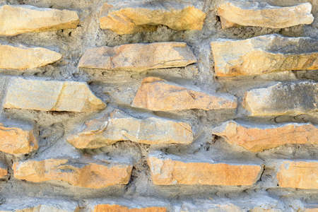 Close-up of wall of beige blocks of Sandstone and cement. Stone texture for interior design and decoration. Concept of construction of buildings and structures made of natural materials