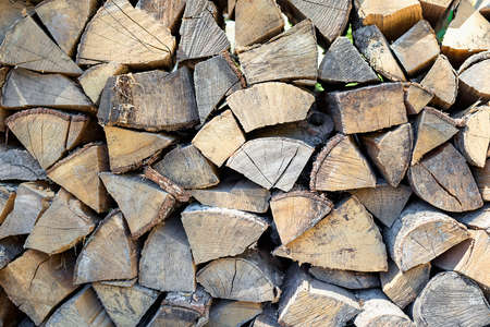 Close-up and selective focus of stack of logs for fireplace and barbecue. Concept of preparation for winter cold season. Chopped wood piled in heap. Texture and pattern for grunge interior design