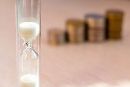 Close-up of hourglass with columns of coins in background. Concept of time to grow personal savings and finance. Change in the value of money. Bank deposits and investments in financial markets 版權商用圖片