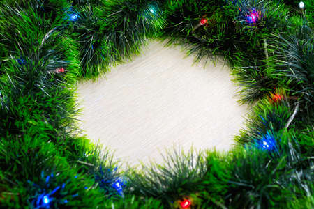 Close-up and soft focus of lignt wooden background and green wreath made of tinsel with burning lights of electric Christmas tree garland with copy space in the middle of it. New year's background