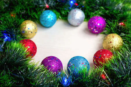 Selective and soft focus of multi-colored shiny Christmas tree balls on wreath of green tinsel and burning electric lights on garland. New year's background and postcard. Holiday home decoration