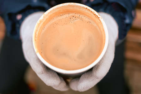 Close-up and soft focus of hot cocoa in white glass in hands of gray cloth gloves. Concept of cold days, autumn and winter season. Warming and hot delicious and healthy drinks. Walks in fresh air