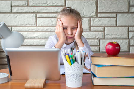 Portrait of a school girl in a white blouse who is sitting at a table and is sad an tired. Back to school and the day of knowledge. Online education. Child does a homework. It's hard to study.