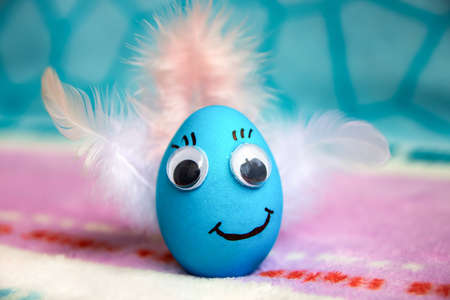 Close-up and selective focus of funny blue Easter egg with painted face and smile, decorated with eyes and feather wings. The concept of children's creativity and preparation for the holiday