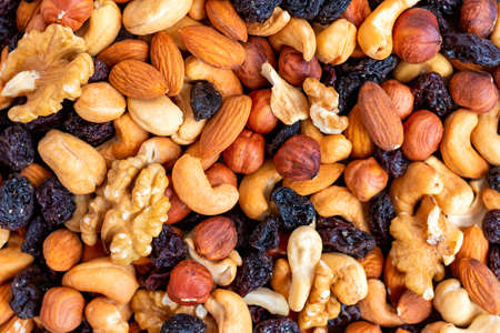 Background and pattern of a mix of different nuts and raisins. The concept of healthy and proper nutrition. Source of vitamins, trace elements, vegetable proteins and fats, oils. Health care Foto de archivo