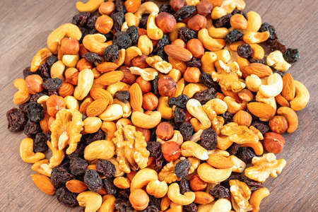 Close-up and selective focus of mix of different nuts and raisins on dark wooden background. Concept of healthy and proper nutrition. Source of vitamins, vegetable proteins and fats, oils. Health care Zdjęcie Seryjne