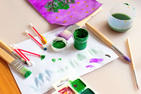 Selective focus of a can of green gouache on a white sheet with stained in paint cotton swabs, a brush, and children's drawings in the background. Concept of kid's art creativity and development