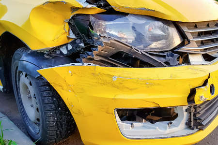Close-up and selective focus of a badly broken yellow taxi car with torn, crumpled and scratched parts after a major accident. The concept of the need for car and life insurance. Mobile photo. Reklamní fotografie