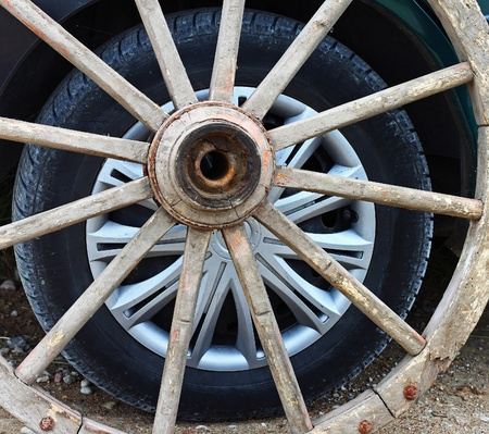 Modern car wheel is visible through the vintage wagon wheel  Old and New technology comparison