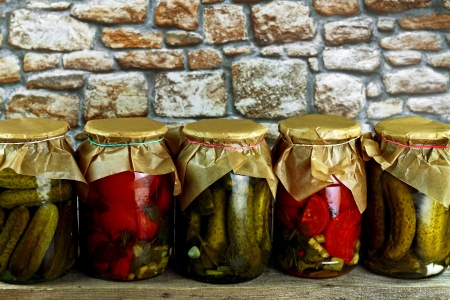 Jars with pickled green cucumbers and red tomatoes on wooden shelf against stone wall Stock Photo