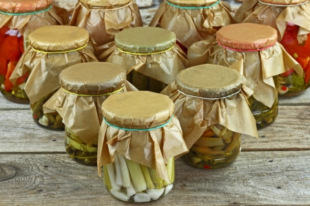 Jars with pickled vegetables arranged in order of bowling pins on wooden shelf against stone wall Stock Photo