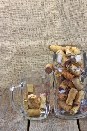 alongside: Wine against beer  Two beer mugs filled with corks from wine bottles are on the rough wooden table  Sackcloth background