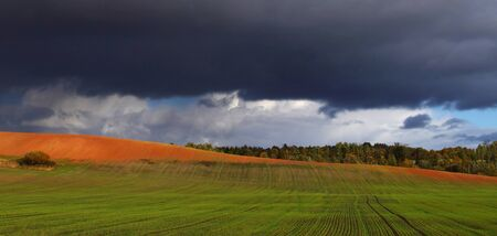 Green meadow and bright hill under dark cloudy sky Stock Photo - 15731287