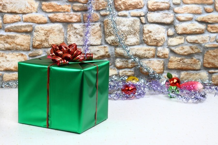Green satin gift box with ribbon and bow against stone wall with Christmas toys and tinsel in background