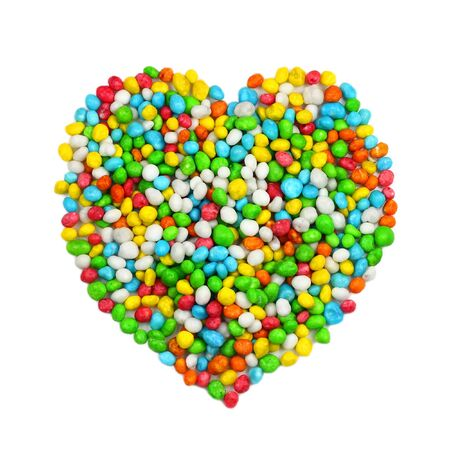 Heart symbol laid out from colorful candies on white with shadows Stock Photo