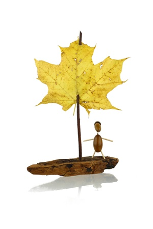 Toy sail boat from pine bark, twig and maple leaf with passenger from acorns isolated on white with shadow Stock Photo
