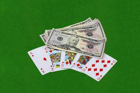 Royal flush combination and thousand of US dollars on green cloth table