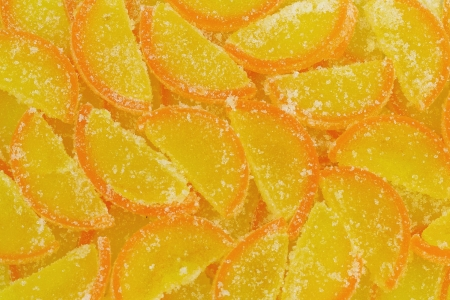 Yellow marmalade imitating orange slices with sugar background