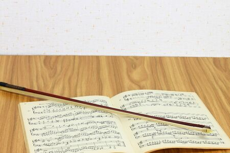 Violin bow over music sheet lie on the table top