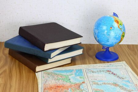 Earth globe, geography maps and books on the table. Educational material on geography