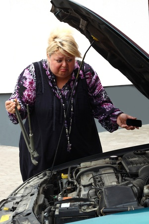 Chubby blond woman trying to repair the car. Desperate effort using absolutely inadequate tool