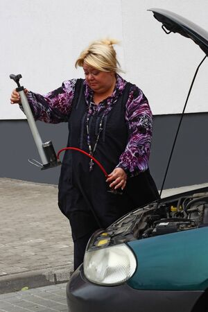 inappropriate: Chubby blond woman is trying to repair her car using absolutely inappropriate tool