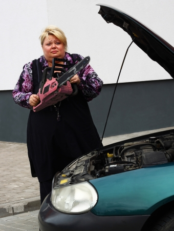 Blond asks for help in repairing the car and offers the most suitable tool for it. It is her lovely pink chainsaw, as she thinks Stock Photo - 16054758