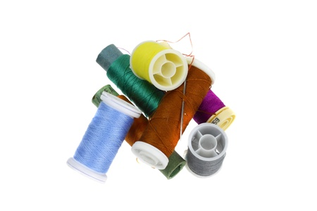 Spools of multicolored embroidery threads in the pile isolated on white Stock Photo