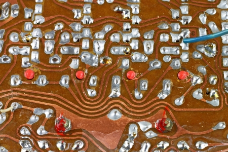 Vintage circuit board surface with tin soldering closeup technological background