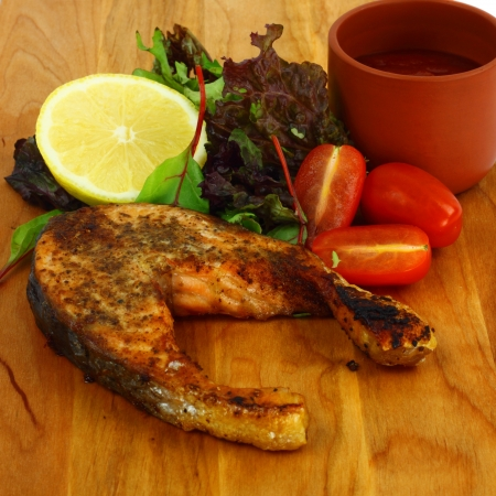Salmon roasted steak served on the wooden board with lemon, lettuce, tomatoes and red sauce photo