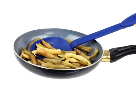 Stewed French bean on the pan with big blue spoon isolated on white background