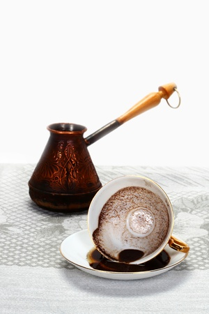 Coffee cup and saucer with a coffee grounds splash on it and vintage turkish coffee maker behind  Divination by a coffee puddles and grounds shape