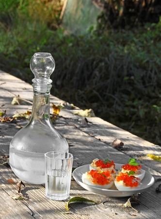 hedonism: Misted decanter of vodka with half full glass and boiled eggs with red caviar on the rough wooden table with shadows outdoor Stock Photo