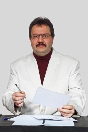 Interested man portrait near the desk on gray background photo