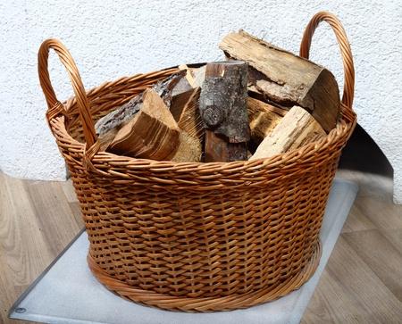 log basket: Wicker basket of firewood on the floor near white oven