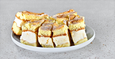 Sponge cakes with white cream and cinnamon on gray table
