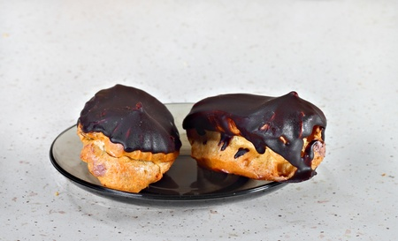 Two eclairs on transparent black plate on gray table