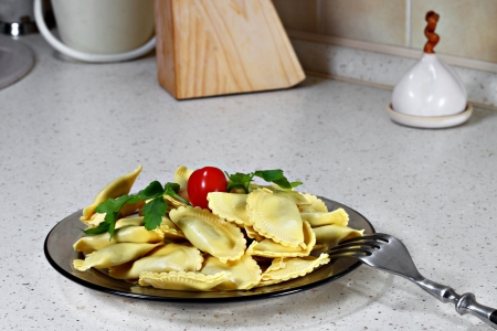 Plate of ravioli with fork on kitchen table Stock Photo
