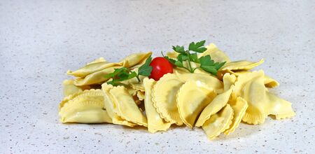 Italian ravioli with green and tomato on table