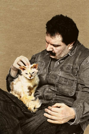 Middle age man with serious fluffy cat portrait. Aged in rough grunge technique