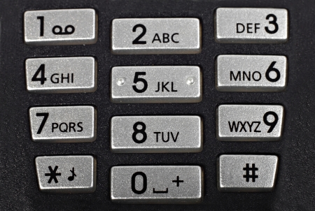 Cell phone keypad, rough black with silver buttons. Macro closeup Stock Photo