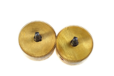 Two massive brass pinions in interlocking isolated on white background Stock Photo