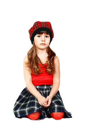 Cute little girl sits dressed in Scottish style  Portrait on white background Stock Photo