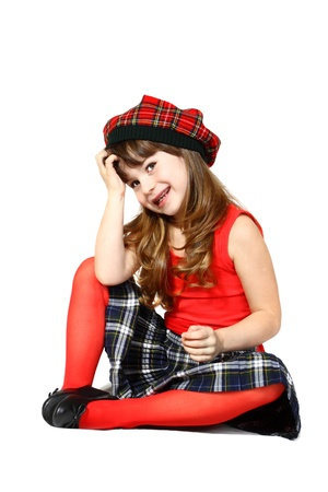 Pretty little girl sits dressed in Scottish style. Portrait on white background with shadows Stock Photo